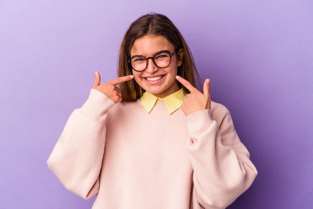 Jeune femme caucasienne isolée sur fond violet sourit, pointant du doigt la bouche.