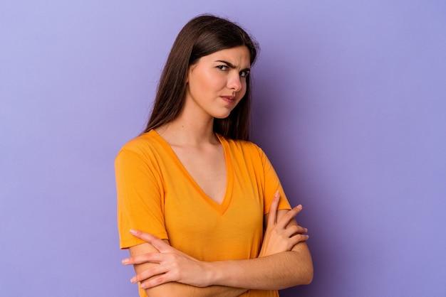 Jeune femme caucasienne isolée sur fond violet suspect, incertain, vous examine.