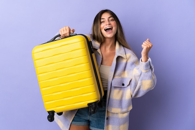 Jeune femme caucasienne isolée sur fond violet en vacances avec valise de voyage