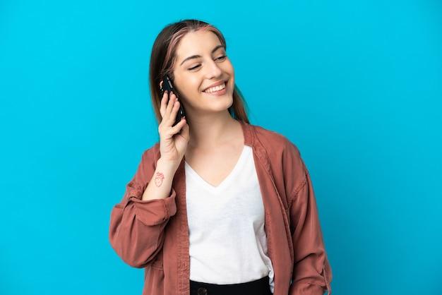 Jeune femme caucasienne isolée en gardant une conversation avec le téléphone mobile avec quelqu'un