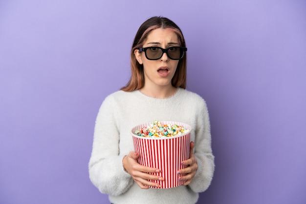 Jeune femme caucasienne isolée avec des lunettes 3d et tenant un grand seau de pop-corn