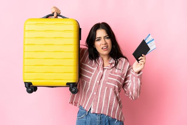 Jeune femme caucasienne isolée malheureuse en vacances avec valise et passeport