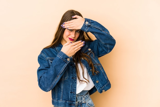 Jeune femme caucasienne isolée en mur beige cligner des yeux à la caméra à travers les doigts, visage couvrant embarrassé.