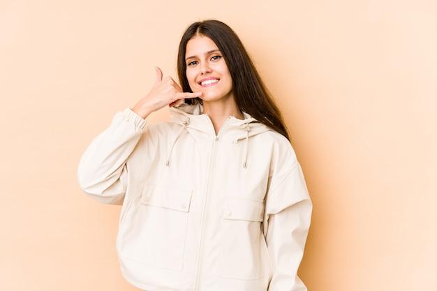 Jeune femme caucasienne isolée sur mur beige montrant un geste d'appel de téléphone mobile avec les doigts.