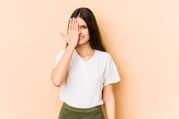 Jeune femme caucasienne isolée sur mur beige s'amuser couvrant la moitié du visage avec la paume.
