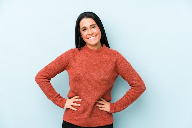 Jeune femme caucasienne isolée sur un mur bleu confiant en gardant les mains sur les hanches.