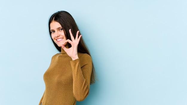 Jeune femme caucasienne isolée sur le mur bleu fait un clin d'œil et détient un geste correct avec la main.