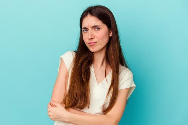 Jeune femme caucasienne isolée sur un mur bleu méfiante, incertaine, vous examinant.