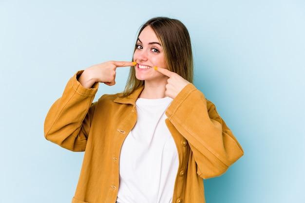 Jeune femme caucasienne isolée sur le mur bleu sourit, pointant du doigt la bouche.