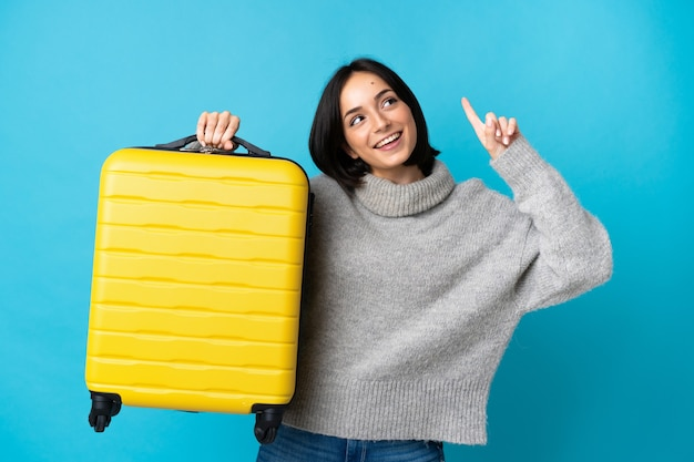 Jeune femme caucasienne isolée sur mur bleu en vacances avec valise de voyage et pointant vers le haut