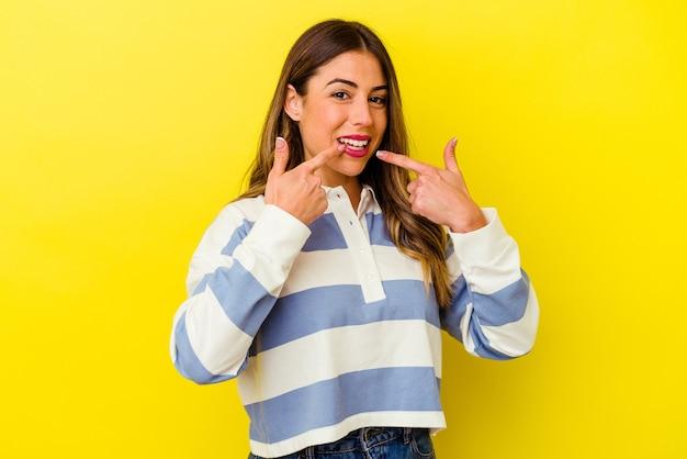 Jeune femme caucasienne isolée sur le mur jaune sourit, pointant du doigt la bouche.