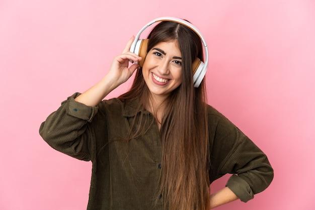 Jeune femme caucasienne isolée sur un mur rose à l'écoute de la musique