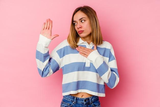 Jeune femme caucasienne isolée sur un mur rose en prêtant serment, mettant la main sur la poitrine.