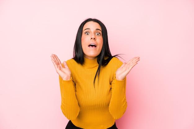 Jeune femme caucasienne isolée sur un mur rose surpris et choqué.