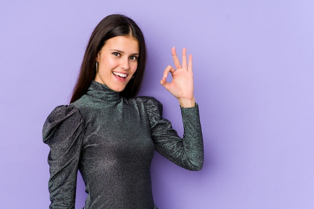 Jeune femme caucasienne isolée sur le mur violet fait un clin d'œil et détient un geste correct avec la main.