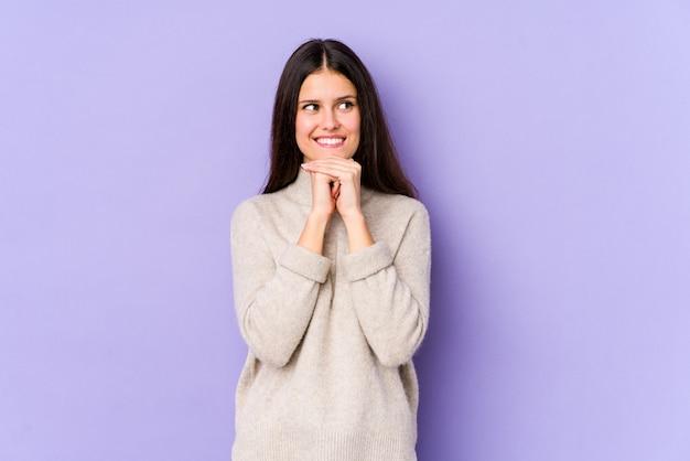 Jeune femme caucasienne isolée sur le mur violet garde les mains sous le menton, regarde joyeusement de côté.