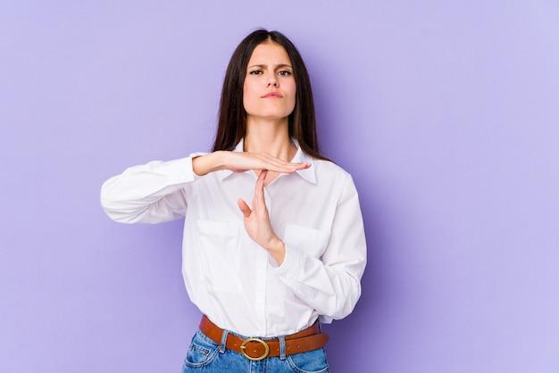 Jeune femme caucasienne isolée sur mur violet montrant un geste de délai d'expiration.