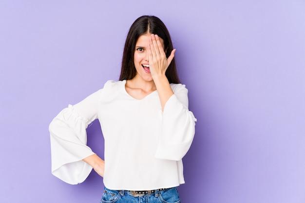 Jeune femme caucasienne isolée sur mur violet s'amuser couvrant la moitié du visage avec la paume.