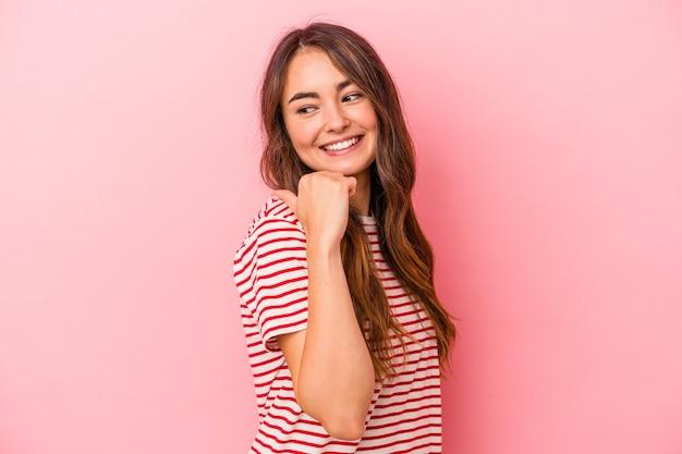 Jeune femme caucasienne isolée sur des points de fond rose avec le pouce loin, riant et insouciant.