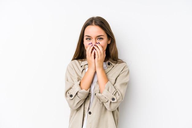 Jeune femme caucasienne isolée rire de quelque chose, couvrant la bouche avec les mains.