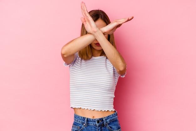 Jeune femme caucasienne isolée sur rose en gardant deux bras croisés, concept de déni.