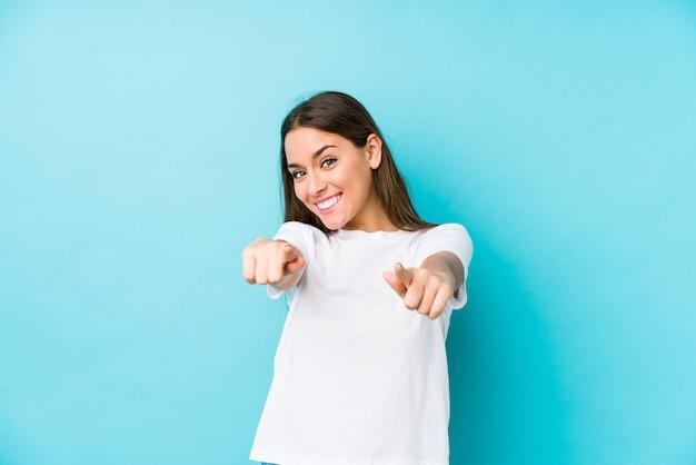 Jeune femme caucasienne isolée sourires joyeux pointant vers l'avant.