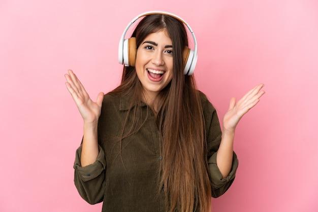 Jeune femme caucasienne isolée surprise et écoute de la musique