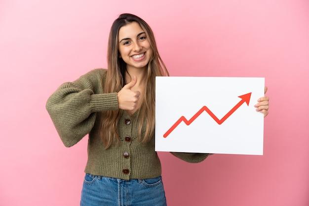 Jeune femme caucasienne isolée tenant une pancarte avec un symbole de flèche de statistiques croissante avec le pouce vers le haut