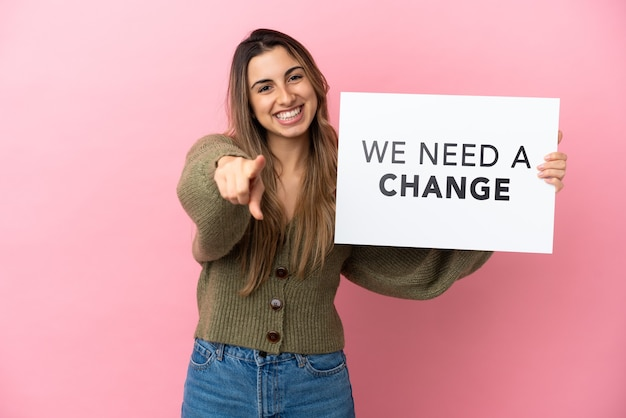 Jeune femme caucasienne isolée tenant une pancarte avec le texte nous avons besoin d'un changement et pointant vers l'avant