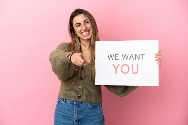 Jeune femme caucasienne isolée tenant le panneau we want you et pointant vers l'avant