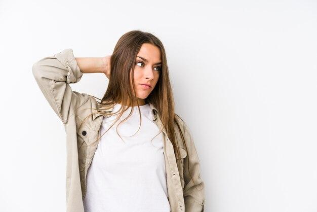 Jeune femme caucasienne isolée toucher l'arrière de la tête, penser et faire un choix.