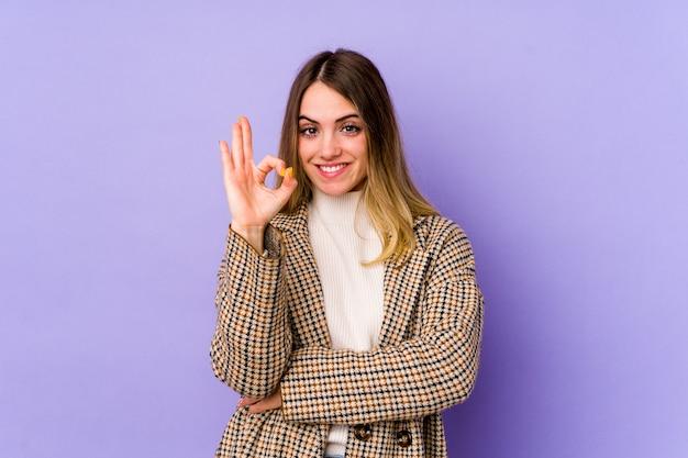Jeune femme caucasienne isolée sur violet cligne de l'œil et détient un geste correct avec la main.