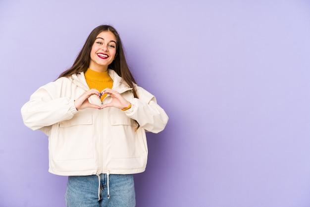 Jeune femme caucasienne isolée sur violet souriant et montrant une forme de coeur avec les mains.