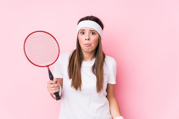 Jeune femme caucasienne jouant au badminton hausse les épaules et les yeux ouverts confus.