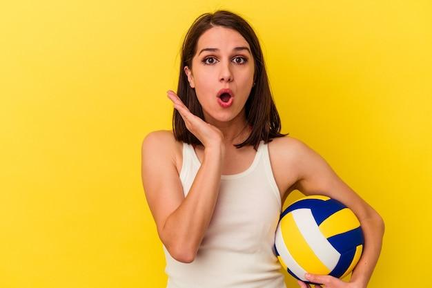 Jeune femme caucasienne jouant au volley-ball isolé sur fond jaune surpris et choqué.
