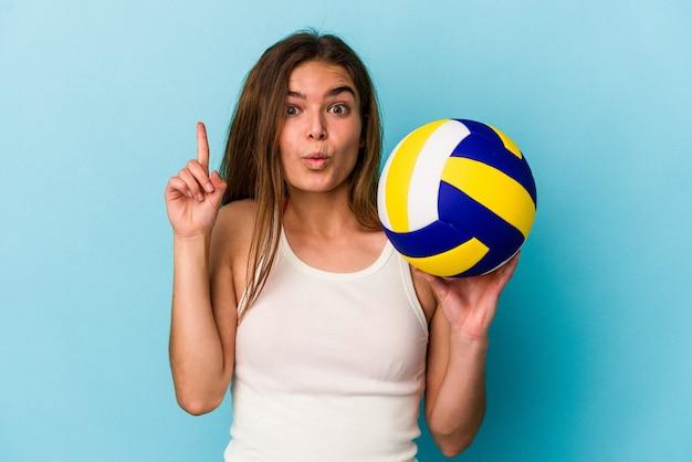 Jeune femme caucasienne jouant au volley-ball isolée sur fond bleu ayant une bonne idée, concept de créativité.