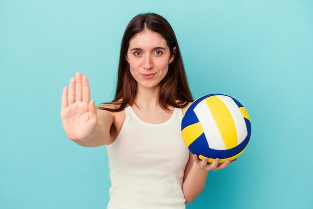 Jeune femme caucasienne jouant au volley-ball isolée sur fond bleu debout avec la main tendue montrant un panneau d'arrêt, vous empêchant.