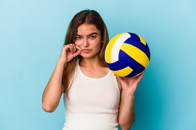 Jeune femme caucasienne jouant au volley-ball isolée sur fond bleu avec les doigts sur les lèvres gardant un secret.