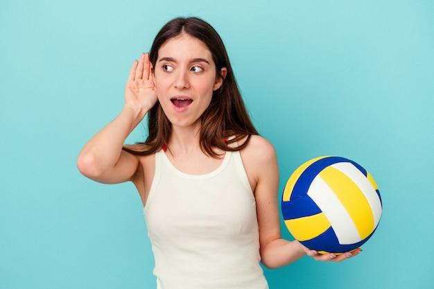Jeune femme caucasienne jouant au volley-ball isolée sur fond bleu essayant d'écouter un potin.