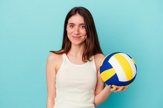 Jeune femme caucasienne jouant au volley-ball isolée sur fond bleu heureuse, souriante et joyeuse.