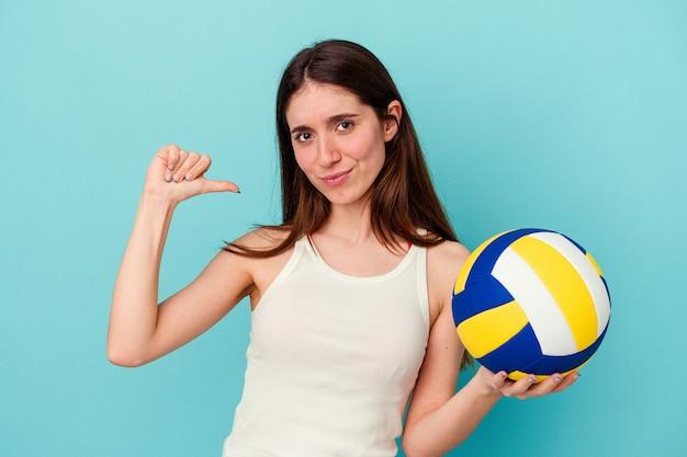 Jeune femme caucasienne jouant au volley-ball isolée sur fond bleu se sent fière et confiante, exemple à suivre.
