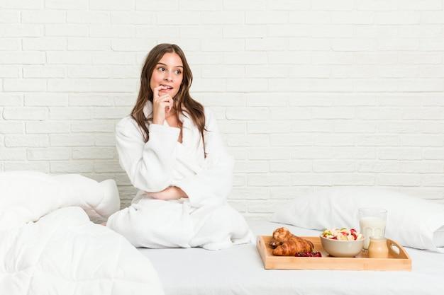 Jeune femme caucasienne sur le lit détendu en pensant à quelque chose en regardant un espace copie.