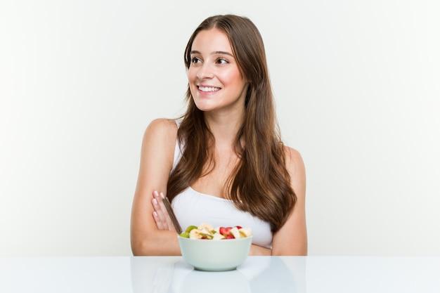 Jeune femme caucasienne, manger un bol de fruits souriant confiant avec les bras croisés.