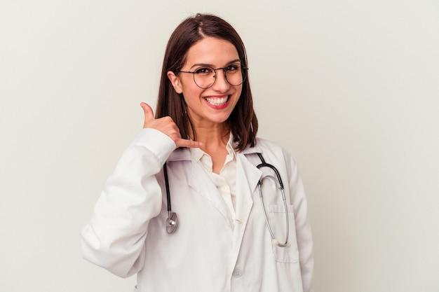 Jeune femme caucasienne médecin isolée sur fond blanc montrant un geste d'appel de téléphone portable avec les doigts.