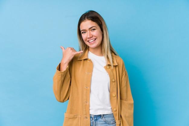 Jeune femme caucasienne montrant un geste d'appel de téléphone mobile avec les doigts.