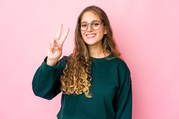Jeune femme caucasienne montrant le signe de la victoire et souriant largement.