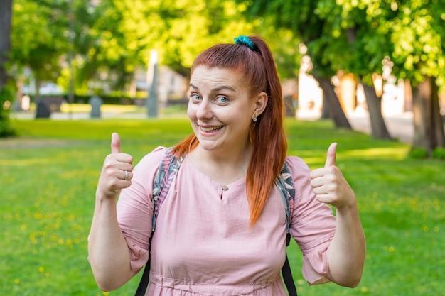 Jeune femme caucasienne montre la main avec les pouces vers le haut. fille romantique à l'extérieur lors d'une journée d'été