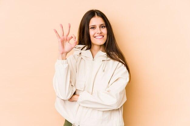 Jeune femme caucasienne sur mur beige cligne de l'œil et tient un geste correct avec la main.