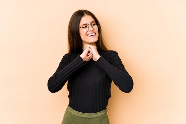 Jeune femme caucasienne sur mur beige garde les mains sous le menton, regarde joyeusement de côté.