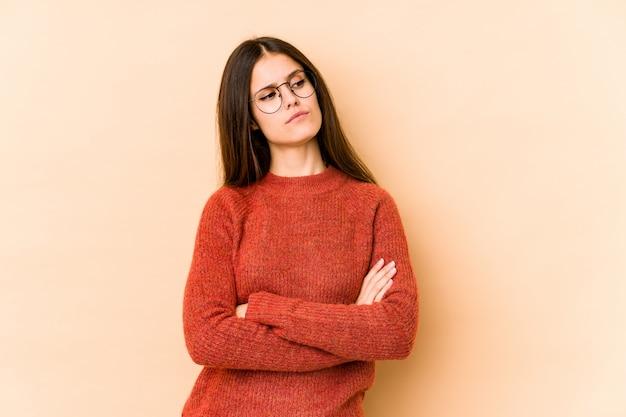 Jeune femme caucasienne sur mur beige rêvant d'atteindre les buts et objectifs